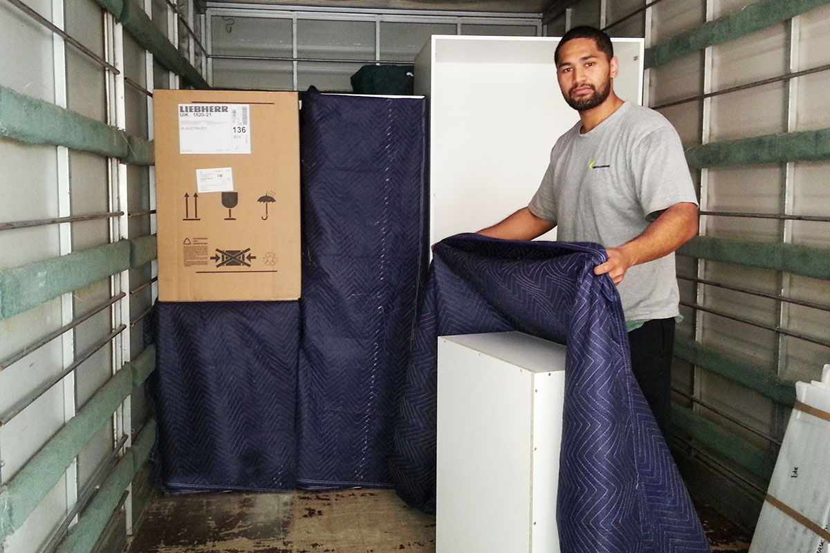 Whangarei removals mover wrapping furniture in a truck